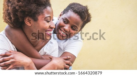 Happy young mother having fun with her kid - Son hugging his mum outdoor - Family connection, motherhood, love and tender moments concept - Focus on boy face