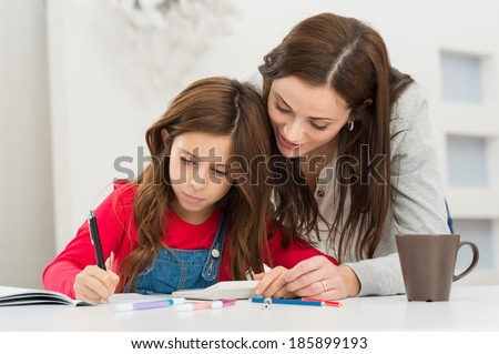 Happy Young Mother Helping Her Daughter While Studying At Home