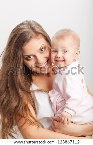 happy young mother  holding her baby girl on hands - stock photo