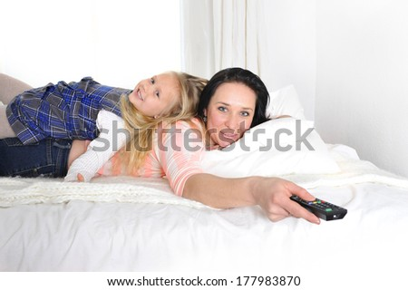 happy young mother holding remote and playful daughter watching television tv lying on bed together