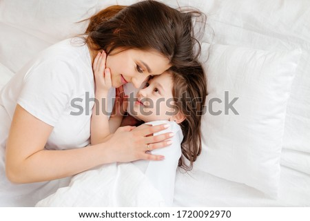 Happy young mother hugs her little daughter in bed, a view from above. mother and daughter rest in bed at home. Good morning!