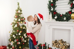 Happy young mother in red hat gently kissing cute little son. Child boy in light room at home with decorated New Year tree and fireplace. Christmas good mood. Family, love and holiday 2018 concept