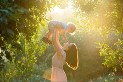 Happy young mother playing and having fun with her little baby son on sunshine warm spring or summer day. Beautiful sunset light in the apple garden or in the park. Happy family concept
