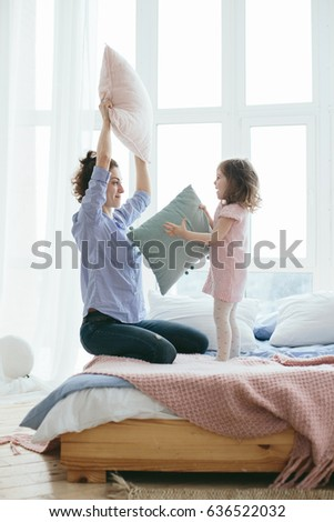 Happy young mother playing pillow fight with her little daughter on the bed in the morning. Having fun together. Joyful family time at home. Pink and blue pastel colors, selective focus.  #636522032
