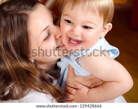 Happy young mother playing with cute son