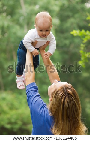 Happy young mother playing with her baby in park