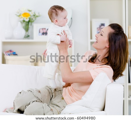 Happy young mother playing with her baby on the sofa - indoors