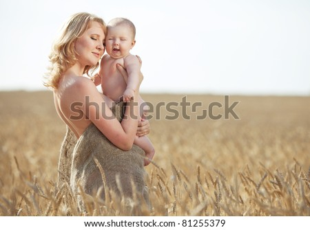 Happy young mother playing with smiling baby girl in park