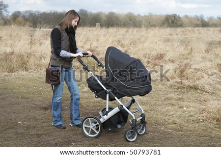 Happy young Mother pushing a pushchair in Richmond Park, London - stock photo