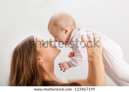 happy young mother rising her baby girl