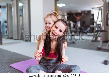 Happy young mother sits on the carpet and keeps on her back her daughter, in the gym