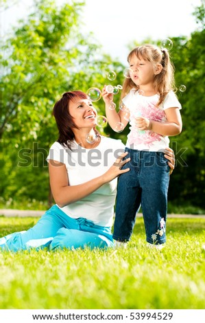 happy young mother sitting in park with her beautiful daughter blowing soap bubbles