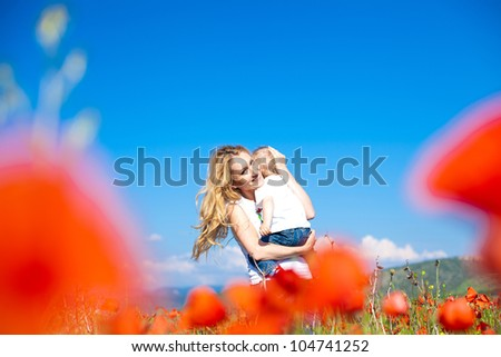 Happy young mother with a child in a poppy field