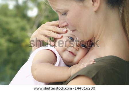 Happy young mother with baby boy lying on sofa at home - stock photo