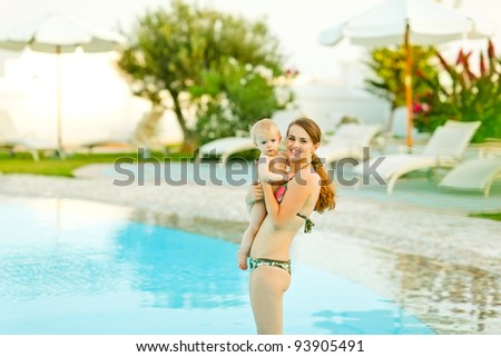Happy young mother with cute baby standing in swimming pool