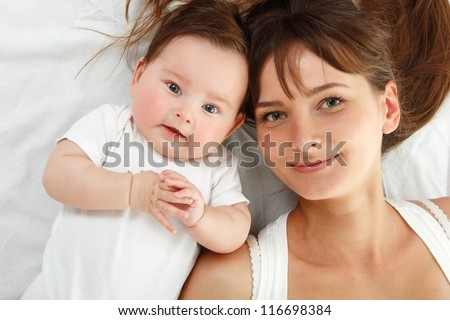 happy young mother with cute smiling baby lying in bed