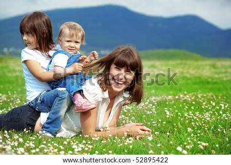 Happy young mother with daughter resting outdoors - stock photo