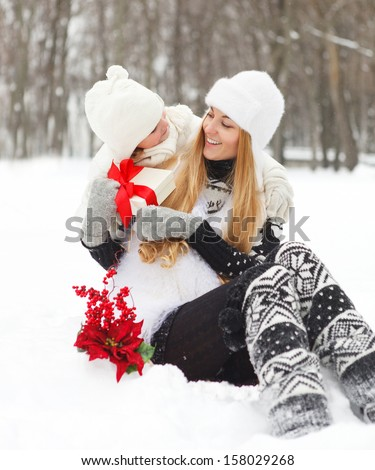 Happy young mother with daughter with present  and christmas decorations on winter picnic