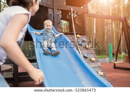 Happy young mother with her baby boy playing in colorful playground for kids. Mom with toddler having fun at summer park. Baby play in children\'s slide