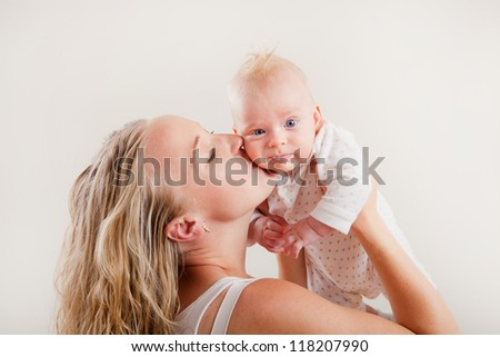 Happy young mother with her baby on white background. Happy family with newborn. - stock photo