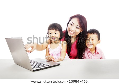 Happy young mother with her children using ultrabook laptop computer to enjoy entertainment