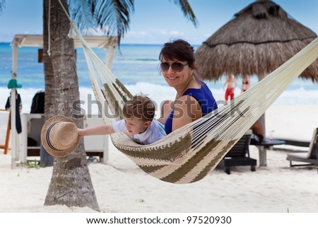 Happy young mother with her son in a hammock on a caribbean beach
