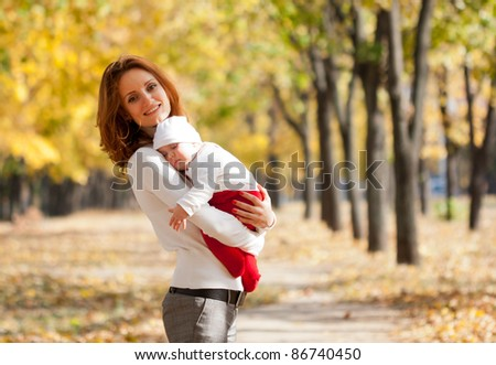 Happy young mother with sleeping child on hands walking in autumn park