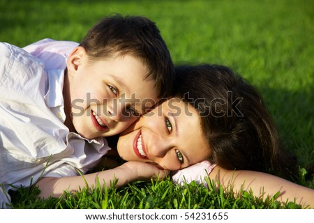 happy young mother with son lying on grass