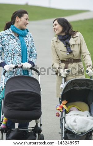 Happy young mothers pushing strollers in park having chat