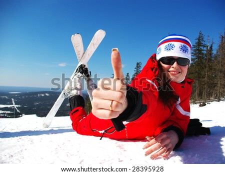 Happy young mountain skier resting on the slope