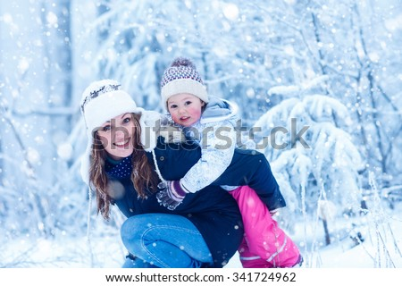 Happy young mum and her little daughter in winter hats in snow forest at snowflakes background. outdoors winter leisure and lifestyle with kids. Beautiful family having fun during snowfall .