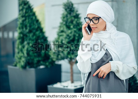 Happy young muslim woman with glasses talking on mobile phone at city street lifestyle portrait. outdoors #744075931