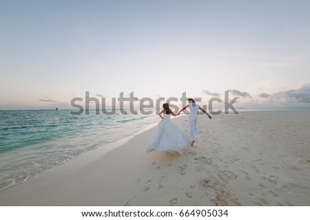 Happy young newly married couple woman in white dress man in love running, have fun on clean sandy beach   waves of azure sea or ocean, summer vacation at water. Wedding rest, relax honeymoon concept. #664905034