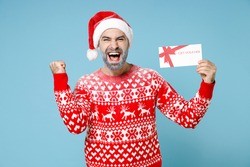 Happy young Northern bearded man frozen face in Santa hat Christmas sweater hold gift certificate doing winner gesture isolated on blue background. Happy New Year merry holiday winter time concept