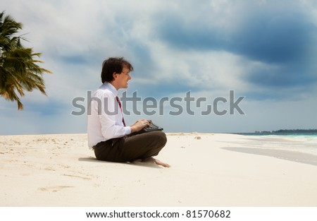 Happy young office worker sitting on the sand near the sea with keyboard