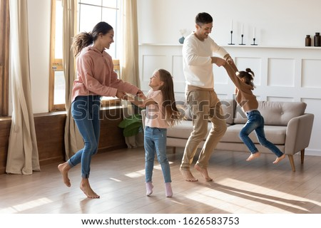 Happy young parents have fun playing with little preschooler excited daughter rest together in living room, smiling family with small kids dancing moving listen to music enjoy weekend at home