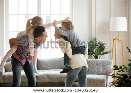Happy young parents piggybacking son and daughter at home, smiling father and mother holding little kids on back spending time together, family having fun enjoying activity playing with children