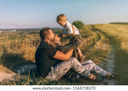 happy young parents sitting and carrying adorable little son in rural landscape #1168738270