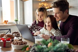 Happy young parents with cute excited small kid daughter using laptop computer at home sitting at Christmas table having virtual party on video call, doing ecommerce family online shopping together.