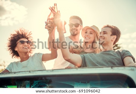Happy young people are clinking bottles of beverage and smiling while travelling by car in sunny weather
