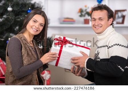 Happy young people are giving each other gifts near the Christmas tree.