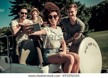 Happy young people are taking photo using a smart phone and smiling while travelling by car in sunny weather
