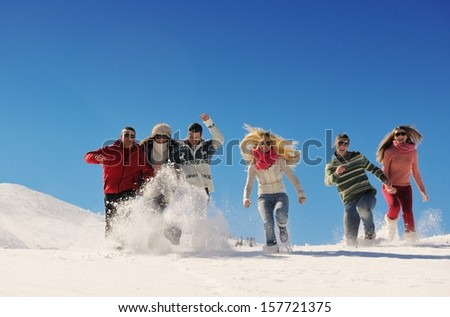 happy young people group have fun and enjoy fresh snow at beautiful winter day