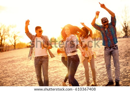 Happy young people having fun on the beach and drinking beer