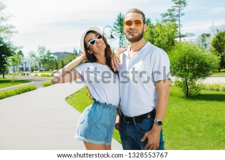 Happy young people in love in the park on a sunny summer day. Summer holidays. Love concept.