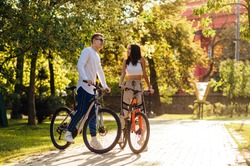 Happy young people in stylish casual clothes riding a bike through a beautiful autumn park. Loving young couple spends active time on bicycles outdoors on a background of sunset.