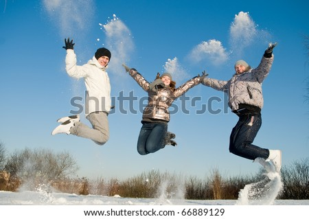 happy young people jumping with snow splashes in winter air