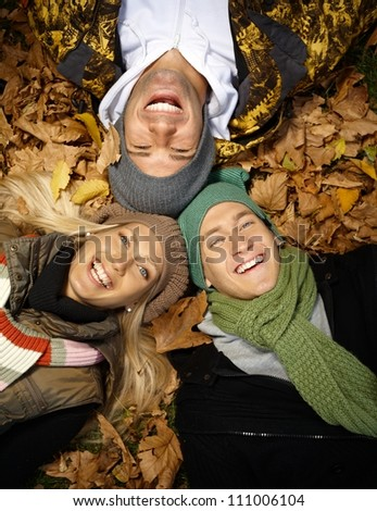 Happy young people laying among leaves in autumn park, laughing, enjoying themselves.