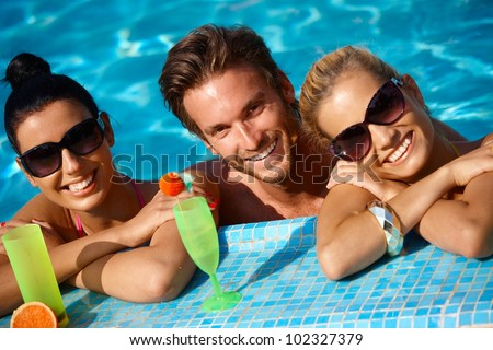 Happy young people on holiday, smiling in swimming pool.