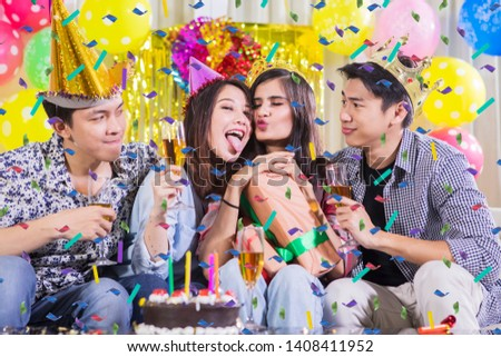 Happy young people taking group photo with silly face expression at a birthday party